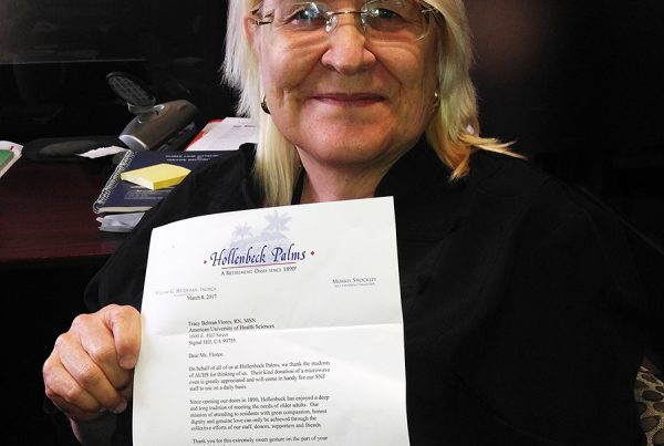 AUHS Professor Tracey Beltran-Flores with a letter from Hollenbeck Palms, thanking her and her Nursing Fundamentals class for donating a microwave in March 2017.